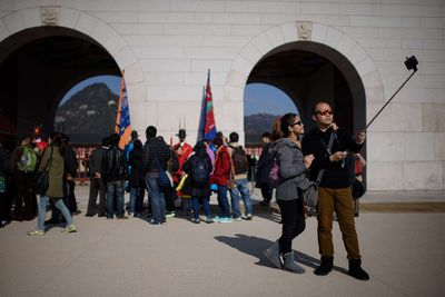 In a photo taken on November 26, 2014 a couple use a 'selfie stick' to take a photo before the Gyeongbokgung palace in central Seoul. In South Korea anyone selling an unregistered bluetooth-enabled selfie stick could face a 27,000 US dollar fine or up to three years in prison, the Science Ministry announced last week. The focus of the ministerial crackdown are those models that come with bluetooth technology, allowing the user to release the smartphone shutter remotely, rather than using a timer. As such they have to be tested and certified to ensure they don't pose a disruption to other devices using the same radio frequency. AFP PHOTO / Ed Jones