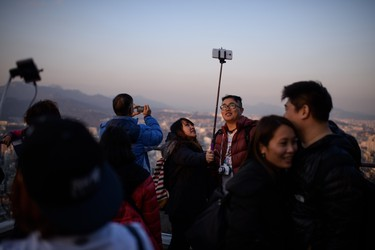 In a photo taken on November 26, 2014 people use a 'selfie stick' to take a group photo overlooking the city skyline in Seoul. In South Korea anyone selling an unregistered bluetooth-enabled selfie stick could face a 27,000 US dollar fine or up to three years in prison, the Science Ministry announced last week. The focus of the ministerial crackdown are those models that come with bluetooth technology, allowing the user to release the smartphone shutter remotely, rather than using a timer. As such they have to be tested and certified to ensure they don't pose a disruption to other devices using the same radio frequency. AFP PHOTO / Ed Jones