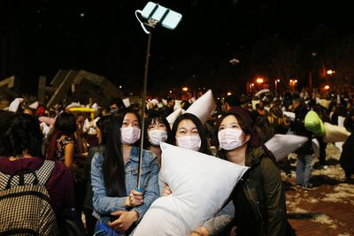 A group of bystanders wearing surgical masks take a photograph with a 'selfie' stick during The Great San Francisco Valentine's Day Pillow Fight, in San Francisco February 14, 2015. Hundreds of people converged on Justin Herman Plaza to belt one another with pillows in the annual unsanctioned event spread through social media. REUTERS/Stephen Lam