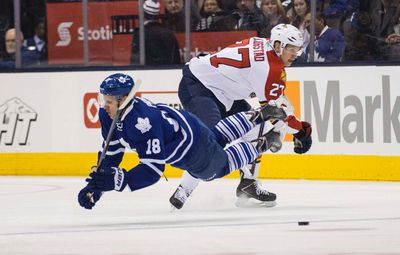 Richard Panik of the Toronto Maple Leafs  gets sent flying by Nick Bjugstad of Florida Panthers during NHL action at the Air Canada Centre  on Tuesday February 17, 2015. Craig Robertson/Toronto Sun/QMI Agency