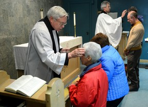 Rev Nick Wells, left, and Dean Kevin Dixon put the mark of the cross on parishioners at St. Paul's Cathedral during their Ash Wednesday service on Wednesday February 18, 2015. (Free Press file photo)