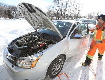 Doug Dauphinais of CAA Manitoba boosts a battery at a member's home in West Kildonan on Thu., Feb. 19, 2015.