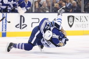Toronto Maple Leafs centre Daniel Winnik (26) takes down Winnipeg Jets defenseman Ben Chiarot (63) as they fight at Air Canada Centre Saturday night. Chiarot was injured in the fight and will miss about six weeks.