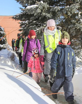 Wesley MacLeod, right, Theresa MacLeod and Isobel MacLeod lead a group of students into James R. Henderson Public School as part of the school's Walking School Bus program. The program runs four mornings a week and gives students the chance to get some exercise along with help with traffic congestion problems at the school in the mornings. (Julia McKay/The Whig-Standard)