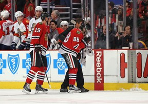 Patrick Kane #88 of the Chicago Blackhawks is helped off the ice in front of Jonathan Toews #19 after being cross-checked against the Florida Panthers at the United Center on February 24, 2015 in Chicago, Illinois.  Jonathan Daniel/Getty Images/AFP