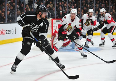 February 26, 2015; Los Angeles, CA, USA; Los Angeles Kings center Anze Kopitar (11) controls the puck against the Ottawa Senators defense during the first period at Staples Center. Mandatory Credit: Gary A. Vasquez-USA TODAY Sports