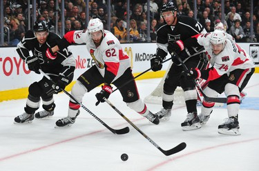 February 26, 2015; Los Angeles, CA, USA; Los Angeles Kings left wing Dwight King (74) and center Jeff Carter (77) play for the puck against Ottawa Senators defenseman Eric Gryba (62) and defenseman Mark Borowiecki (74) during the first period at Staples Center. Mandatory Credit: Gary A. Vasquez-USA TODAY Sports
