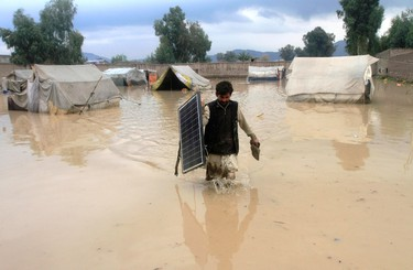 An Afghan man carries a solar panel as he wades through flood waters in the Behsud District of Nangarhar province, Feb. 25, 2015. Four people were killed and hundred houses have been damaged after a heavy rain and flood, provincial spokesman Ahmadzia Abdulzai said. (REUTERS/Parwiz )
