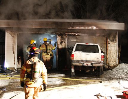 Grande Prairie firefighters inspect the inside of a garage, after putting out a fire in the garage on 110 Avenue behind a home on 96 Street in Grande Prairie on Friday, Feb. 27, 2015. ALEXA HUFFMAN/DAILY HERALD TRIBUNE/QMI AGENCY