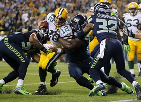 Green Bay Packers quarterback Aaron Rodgers (12) is tackled three yards from the endzone by Seattle Seahawks Bobby Wagner (54), Clinton McDonald (69) and Jeron Johnson (32) during the fourth quarter of their Monday night NFL football game at Centurylink Field in Seattle, Washington, September 24, 2012.  (REUTERS)