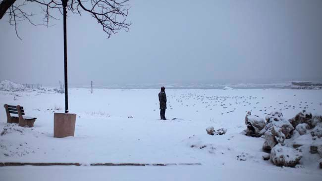 A man stands in falling snow at the shore of the Hudson River in the New York City suburban town of Nyack, New York March 1, 2015.   REUTERS/Mike Segar