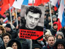 "A portrait of Kremlin critic Boris Nemtsov, who was shot dead on Friday night, is seen during a march to commemorate him in central Moscow March 1, 2015. Holding placards declaring ""I am not afraid"", thousands of Russians marched in Moscow on Sunday in memory of Nemtsov, whose murder has widened a split in society that some say could threaten Russia's future. The words under the portrait reads ""These bullets are meant for each of us"". REUTERS/Maxim Shemetov"