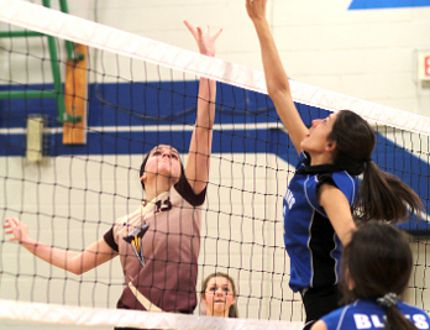 Jocie Breton, left, of the Thériault Jr. Flammes and Andrea Pintar of the TH&VS Jr. Blues go up for a ball on Tuesday, as the two teams clashed in the NEOAA girls high school volleyball championship finals. The Blues claimed the title with a straight-set 25-17, 25-17 win. BENJAMIN AUBÉ/The Daily Press