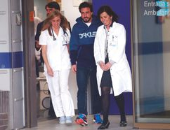 McLaren's Fernando Alonso (centre) walks with medical staff as he leaves a hospital after suffering a concussion. (REUTERS)