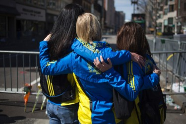 Boston Marathon runners (L to R) Lisa Kresky-Griffin, Diane Deigmann and Tammy Snyder embrace at the barricaded entrance at Boylston Street near the finish line of the Boston Marathon in Boston, Massachusetts April 16, 2013.  REUTERS/Shannon Stapleton