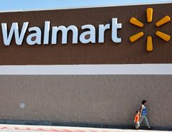 People walk past a Walmart sign in this June 4, 2009 file photo. (REUTERS/Jessica Rinaldi/Files)