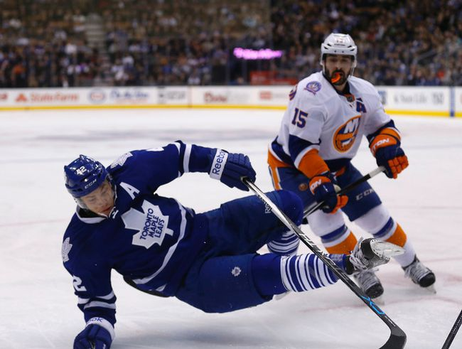 The Isles' Cal Clutterbuck knocks down Leafs centre Tyler Bozak on Monday night at the ACC. MICHAEL PEAKE/TORONTO SUN)