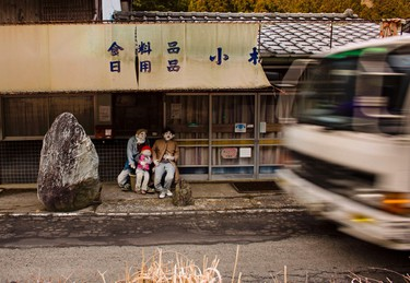 A vehicle drives past scarecrows sitting outside a closed down shop in the village of Nagoro on Shikoku Island in southern Japan on Feb. 24, 2015. (REUTERS/Thomas Peter)