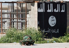 A member of militias known as Hashid Shaabi kneels as he celebrates victory next to a wall painted with the black flag commonly used by Islamic State militants, in the town of al-Alam on March 10, 2015. (REUTERS/Thaier Al-Sudani)