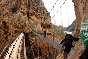 Journalists take pictures as they walk along the new Caminito del Rey (The King's Little Pathway) in El Chorro-Alora, near Malaga, southern Spain March 15, 2015. Dubbed by many media outlets as the world's scariest pathway, the three-kilometre long pathway, which was built at about 100 metres above the gorge of Los Gaitanes between the years of 1901 and 1905, was closed in 2001 after five people died. A new walkway has then been built over the old walkway and will open to the public on March 28, 2015. REUTERS/Jon Nazca