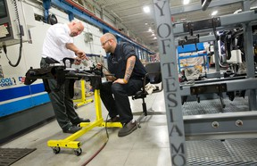 Technical sales representative Don Wilson, left, consults with operator Shawn Ridley as they make parts to be shipped to electric sports car maker Tesla at Attica Manufacturing on Invicta Court. (QMI Agency file photo)