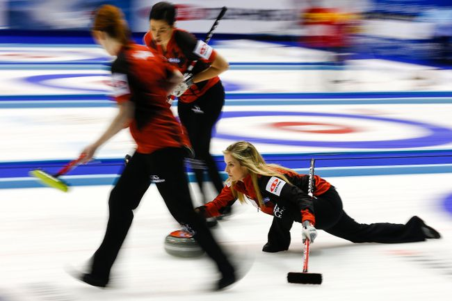 Canada's skip Jennifer Jones delivers a stone as her teammates Dawn McEwen and Jill Officer prepare to sweep during their curling round robin game against the U.S. at the World Women's Curling Championships in Sapporo March 17, 2015. (REUTERS/Thomas Peter)