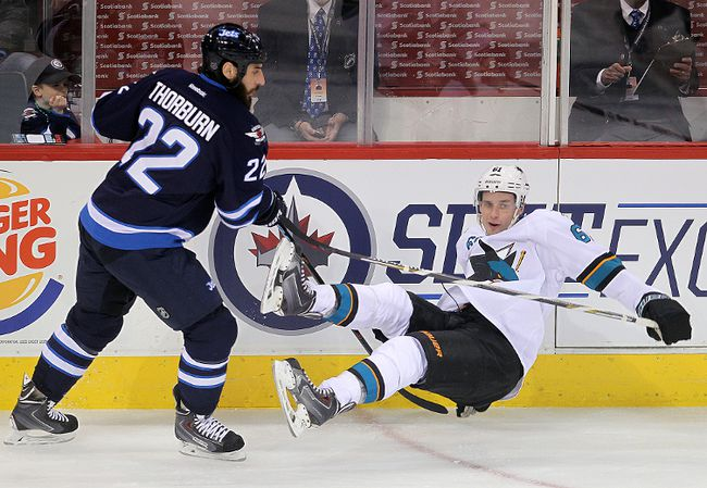 Winnipeg Jets right winger Chris Thorburn (l) dumps San Jose Sharks defenceman Justin Braun during NHL hockey in Winnipeg, Man. Tuesday, March 17, 2015.