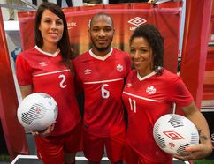 (left to right) Canadian National Soccer Team members Emily Zurrer, Julian de Guzman and Desiree Scott model the new Canada kit that Canada's National Soccer Teams will be wearing in 2015, during a press conference at the West Edmonton Mall Sport Chek on Friday. (David Bloom, Edmonton Sun)
