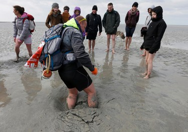 Sebastien Daligault, a guide at the Bay Saint-Michel, stands knee-deep in quicksand as tourists watch nearby during a walking tour at low tide around the Mont Saint-Michel off France's Normandy coast March 21, 2015. At the Mont Saint-Michel 11th century abbey, where some of the biggest tides in the world occur, visitors gathered to watch the tide disappear out of sight, exposing areas of beach and rock visible only every 18 years. REUTERS/Pascal Rossignol