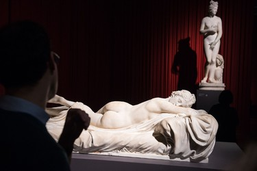 """A man looks at a marble figure of Hermaphroditos (1st-2nd century AD), displayed during a press preview of the British Museum's """"Defining beauty: the body in ancient Greek art"""" in central London on March 24, 2015. Running from march 26 to July 5 2015, the exhibition explores the Greek preoccupation with the human form, and features around 150 objects. These include bronzes and vases as well as iconic white marble statues and sculptures. AFP PHOTO / LEON NEAL"""