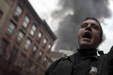 A New York Police Department (NYPD) officer shouts towards residents while clearing the site of a building fire in the East Village neighborhood of New York City on March 26, 2015. A residential apartment building collapsed and was engulfed in flames on Thursday in New York City's East Village neighborhood, critically injuring at least one person, authorities said.  REUTERS/Ben Hider
