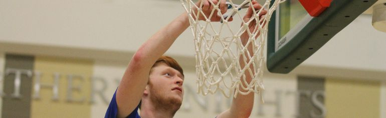 Zach Persson from the St. Peter the Apostle seniors boys basketball team takes part in the championship tradition of cutting down the nets after the Spartans raged to an 88-56 win over Leduc Composite HIgh School in Alberta's 3A provincial championship game on March 21 in Fort McMurray. - Robert Murray, Fort McMurray Today