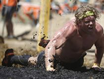 A man screams as he is shocked by electric wires as he scrambles through mud during the Tough Mudder 10-12 mile obstacle challenge in San Bernardino