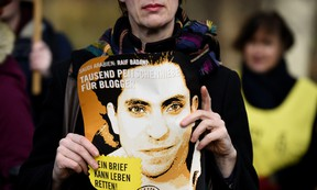 An Amnesty International activist holds a picture of Saudi blogger Raif Badawi during a protest against his flogging punishment on Jan. 29, 2015 in front of Saudi Arabia's embassy to Germany in Berlin. (AFP PHOTO/TOBIAS SCHWARZ)