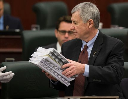 Alberta finance minister Robin Campbell holds budget documents before delivering Budget 2015 in the Alberta Legislature in Edmonton, Alta., on Thursday, March 26, 2015.