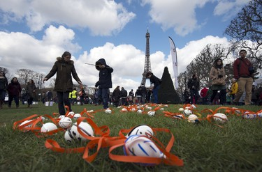 """Children take part in an Easter egg hung organized by the French non-profit organization """"Secours populaire"""" at the Champ de Mars in front of the Eiffel Tower in Paris on April 5, 2015. AFP PHOTO/MIGUEL MEDINA"""