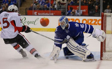 Ottawa Senators Cody Ceci tries to slip the puck under the stick of Toronto Maple Leafs Jonathan Bernier (45) G�but is stopped in the  third period in Toronto on Monday April 6, 2015. Jack Boland/Toronto Sun/QMI Agency
