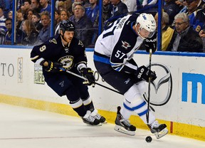Winnipeg Jets defenseman Tyler Myers (57) controls the puck in front of St. Louis Blues center Steve Ott (9) during the second period at Scottrade Center. (Jasen Vinlove-USA TODAY Sports)