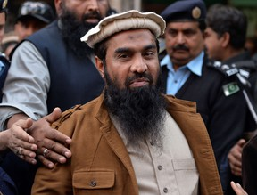 Pakistani security personnel escort Zaki-ur-Rehman Lakhvi, centre, alleged mastermind of the 2008 Mumbai attacks, as he leaves the court after a hearing in Islamabad in this Jan. 1, 2015 file photo. (AFP PHOTO/Aamir Qureshi/FILES)