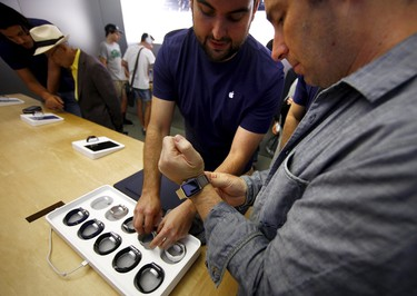 Customer Peter Watling is assisted by a staff member of the Sydney Apple store as he tries on an Apple Watch after it went on display April 10, 2015.  REUTERS/David Gray