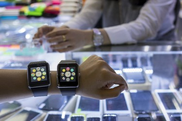 A salesman poses with two Apple Watch lookalike devices, made by a Chinese manufacturer, at a mall selling electronic products in China's southern city of Shenzhen April 8, 2015. REUTERS/Tyrone Siu