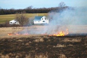 Prince Edward County firefighters are busy fighting a stubborn blaze in a Sophiasburgh marsh early Saturday morning, April 11, 2015. The fire broke out around 2 a.m. in the marsh between County Road 15 and Big Island, east of the causeway. Above, firefighters remained on scene well into the day, fighting small pockets of flames spread out over the huge marsh area. - Bruce Bell/Belleville Intelligencer/QMI Agency