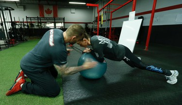 """Canadian UFC fighter Jessica """"Ragin"""" Rakoczy  trains at the EPC centre with her trainer Joe Arko (L) in Burlington, Ont. on Thursday April 9, 2015. She will be on the card at UFC 186 in Montreal at the Bell Centre fighting Valerie Letourneau on Saturday April 25. Jack Boland/Toronto Sun/QMI Agency"""