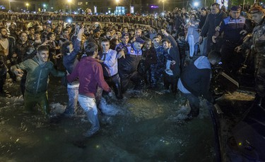 U.S. rapper Kanye West (3rd R in the water, facing the camera), husband of U.S. television personality Kim Kardashian, walks out of a lake, together with security guards, policemen and fans, during a concert in Yerevan, early April 13, 2015. West tried to walk on water in Armenia in the early hours of Monday morning after jumping into a lake. Towards the end of a free concert he was performing in Yerevan, West decided to dive into the city's Swan Lake and dozens of his fans followed suit. REUTERS/Vahan Stepanyan/PAN Photo