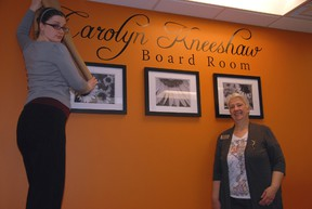St. Thomas Public Library marketing coordinator Ruth Crocker, left, and CEO/chief librarian Rudi Denham unviel the artwork in the second floor board room dedicated in the memory of of long-serving former CEO/chief librarian Carolyn Kneeshaw.