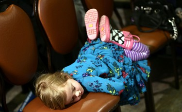A young girl takes a nap in the front row as Premier Jim Prentice speaks during a PC rally at Whitemud Creek Community Centre in Edmonton on Tuesday, April 14, 2015. (Perry Mah/Edmonton Sun/Postmedia Network)