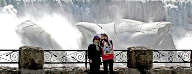 Tourists gather around Niagara Falls in the mild sunny conditions for a look at the mighty cataracts, where the icy grip of winter is not letting go so easily on Monday, April 13, 2015. (Mike DiBattista/Niagara Falls Review/Postmedia Network)