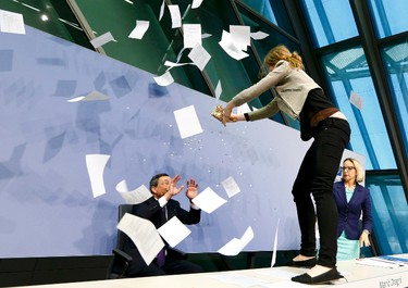 A protester jumps on the table in front of the European Central Bank President Mario Draghi during a news conference in Frankfurt, Germany, April 15, 2015. The news conference was disrupted on Wednesday when a woman in a black T-shirt jumped on the podium. (REUTERS/Ralph Orlowski)