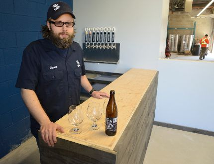 Dave Reed, co-owner of Forked River Brewing Company, stands by the half finished front desk where they had hoped to be selling beer from the brewery. Red tape has thrown a wrench in their plans. (MORRIS LAMONT, The London Free Press)