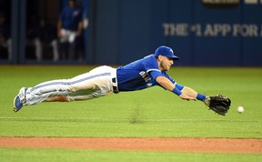 Toronto Blue Jays shortstop Steve Tolleson dives for a ball hit by Atlanta Braves shortstop Andrelton Simmons in the seventh inning Saturday at Rogers Centre. (Dan Hamilton/USA TODAY Sports)